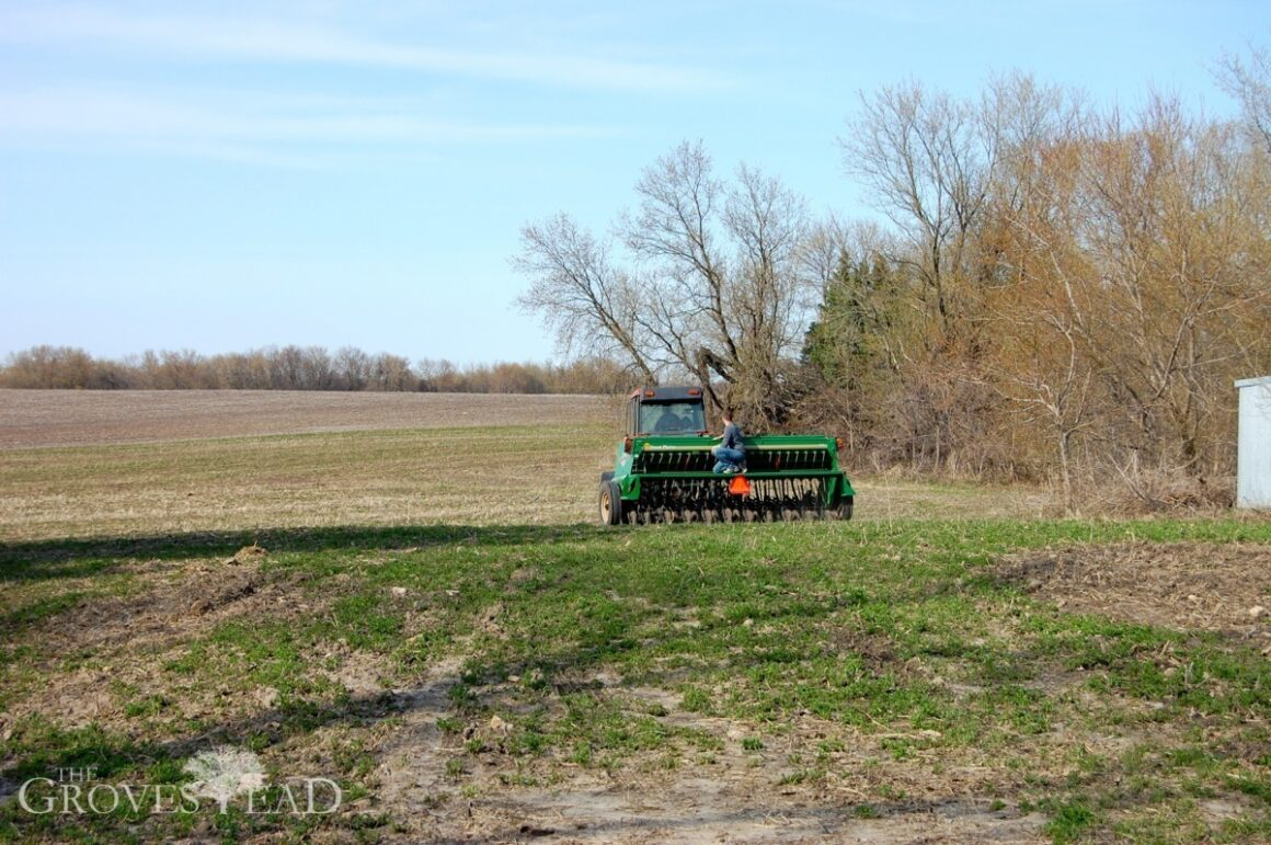 Riding on the seed drill while tractor is planting field