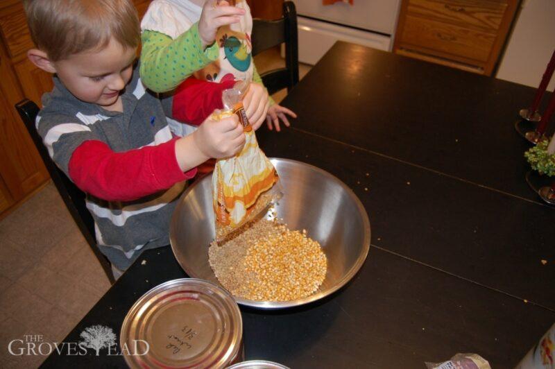 Dumping corn kernals into homemade chicken feed