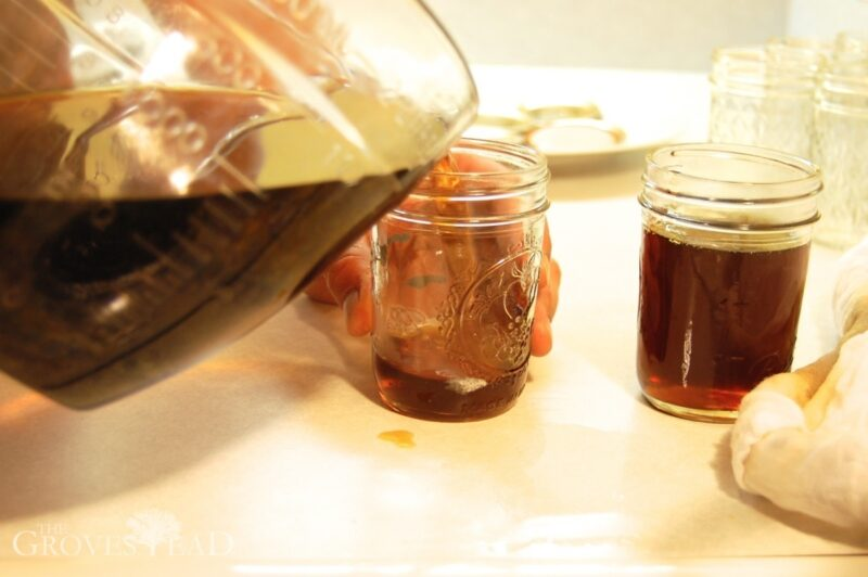 Pouring filtered maple syrup into jars