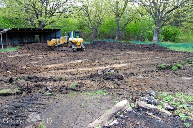 Bull dozer prepares the site pad for new barn construction
