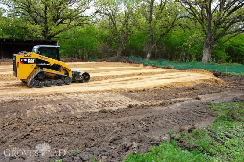 Skid loader smoothes out clay pad