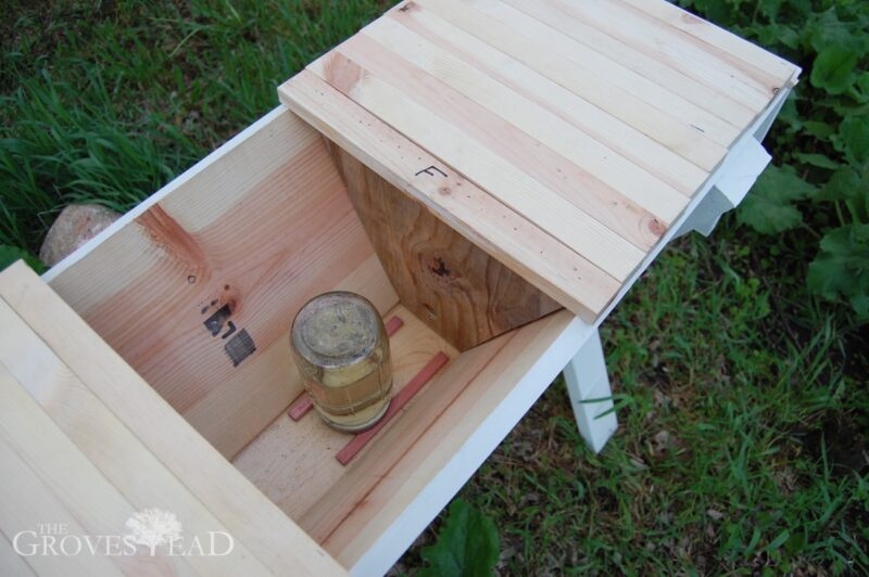 Inside a top bar beehive showing feeder behind follower